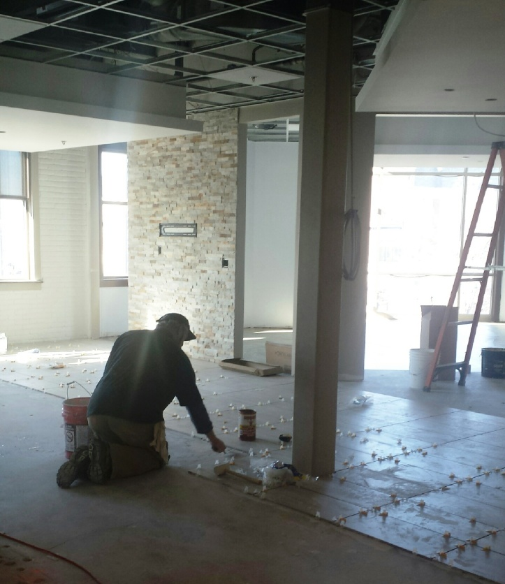 Worker installing floor tile