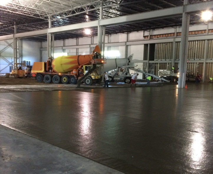 Contractors pour the new 174,000 SF shop floor with cement 8 inches thick.