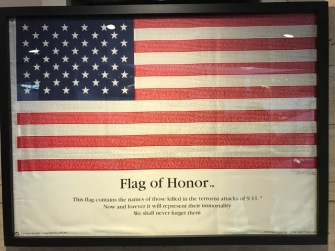 A flag with the names of all of the victims is proudly displayed at the FCA US headquarters next to the World Trade Center display.