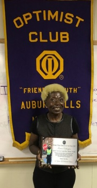 Ms. Eddington with her award at the Auburn Hills Morning Optimist Club meeting.