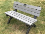 A park bench with an engraved plaque reads: In honor of Leonard Hendricks, a visionary leader and first City Manager of Auburn Hills.